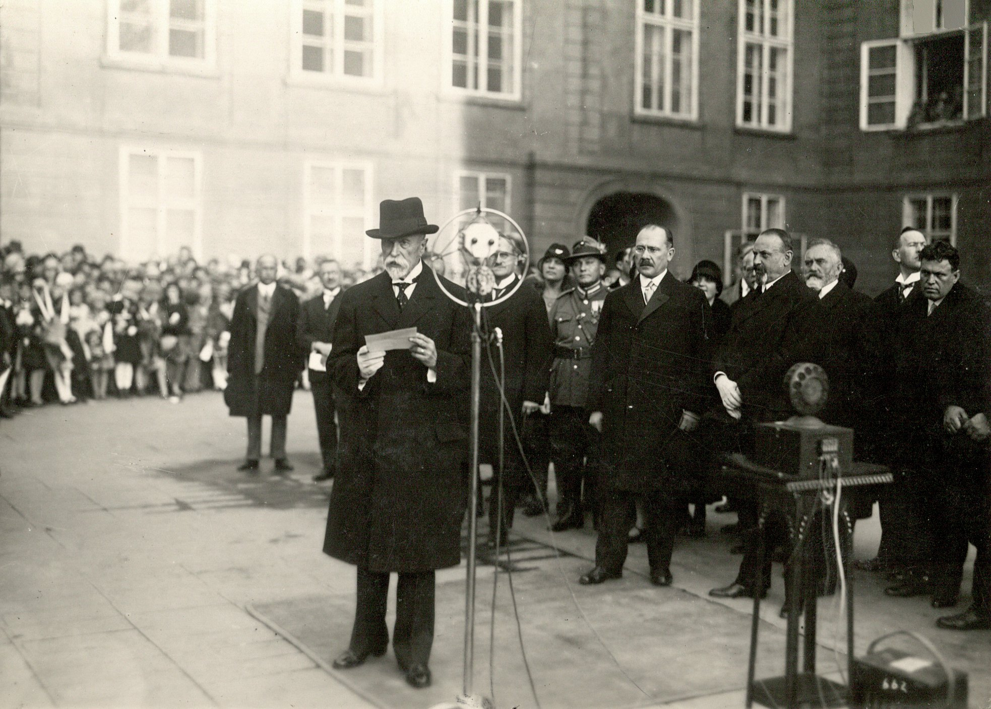 Prezident T. G. Masaryk hovoří ke školní mládeži. Rozhlasový přenos z Pražského hradu při oslavách 10. výročí republiky 27.10.1928, za Masarykem stojí ministr školství Milan Hodža a kancléř Přemysl Šámal