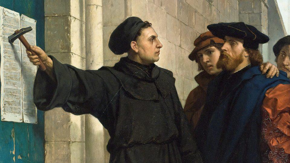 Kazatel Martin Luther přibijí na dveře kostela v německém Wittenbergu svých 95 tezí, 1517