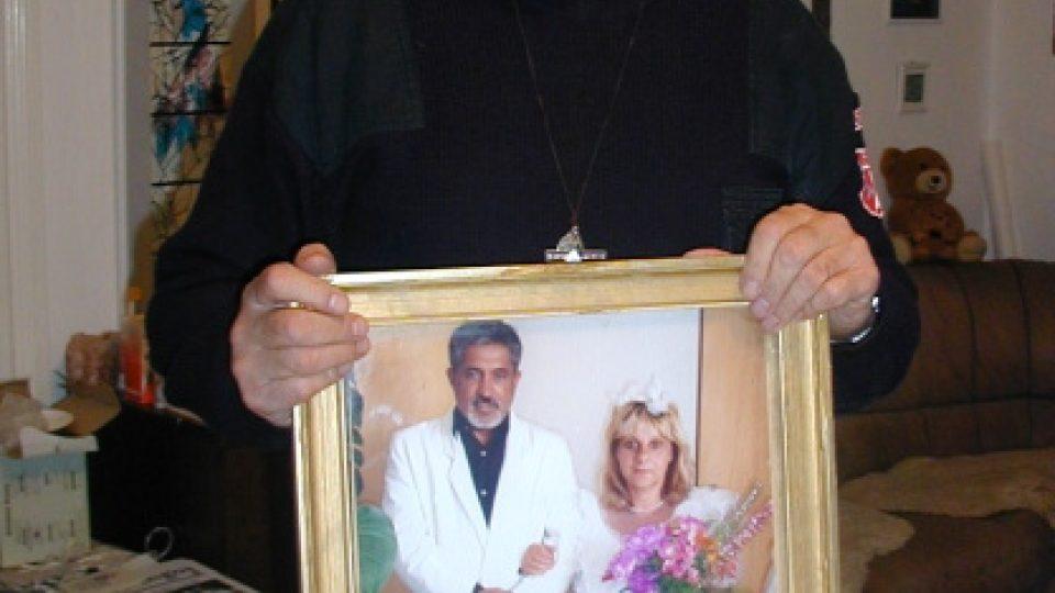 Páter František Lízna ukazuje svatební fotografii rodičů svého romského svěřence Patrika