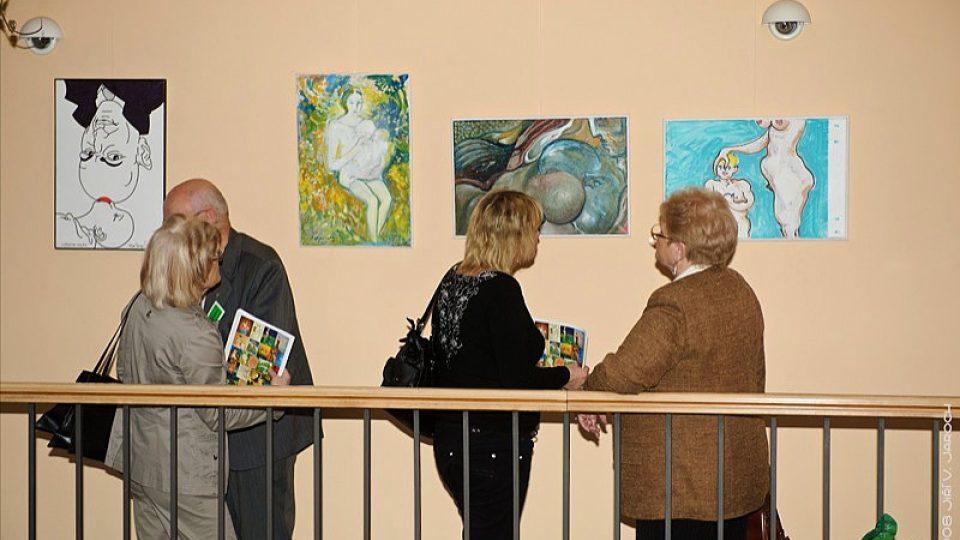 """lidé obdivují výstavu """"Výtvarníci proti týrání žen a dětí""""."""