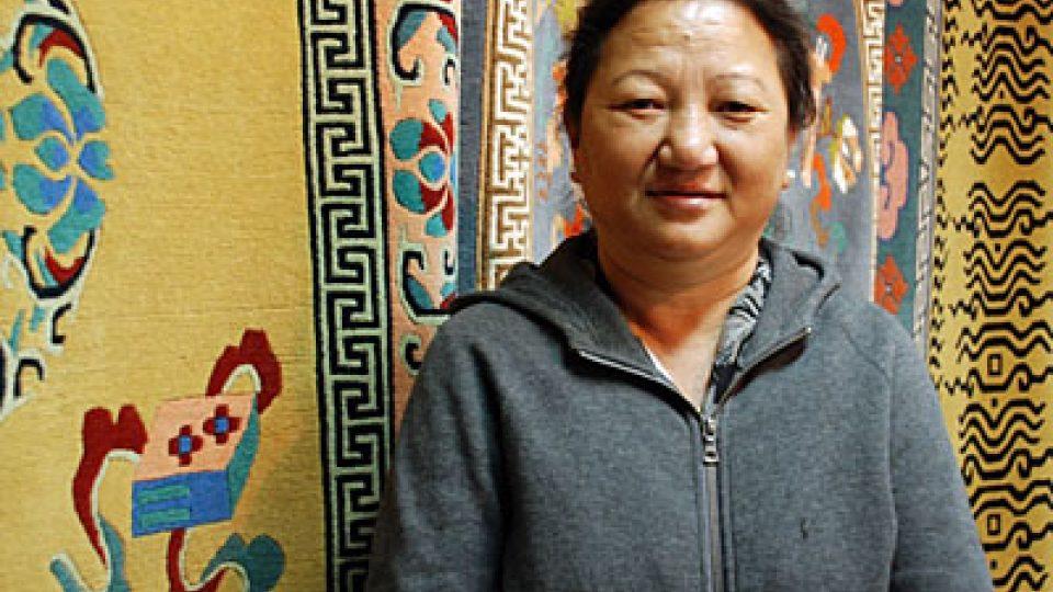 Tibeťanka Amrita před tibetskými koberci
