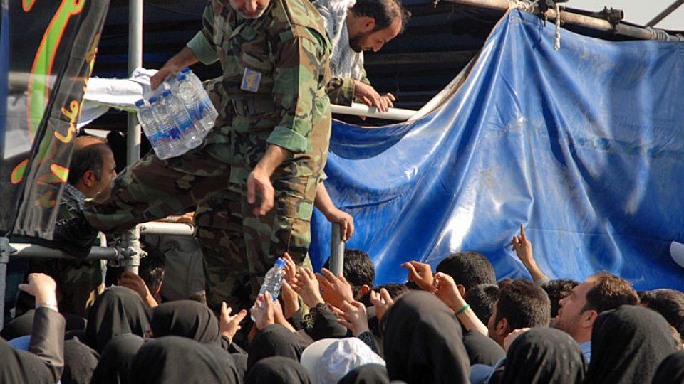 Příslušník revolučních gard rozdává vodu
