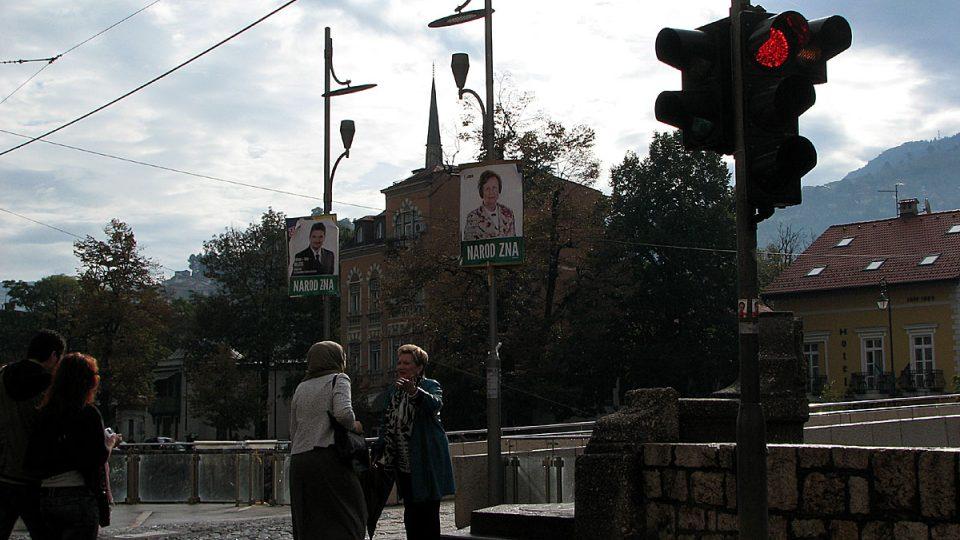 Přátelský rozhovor dvou žen na sarajevské křižovatce pod volebními plakáty
