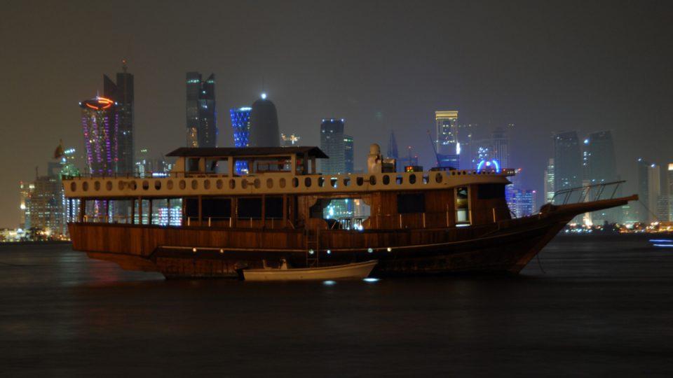 Tradiční loď katarských rybářů a lovců perel na pozadí moderního města Dauha