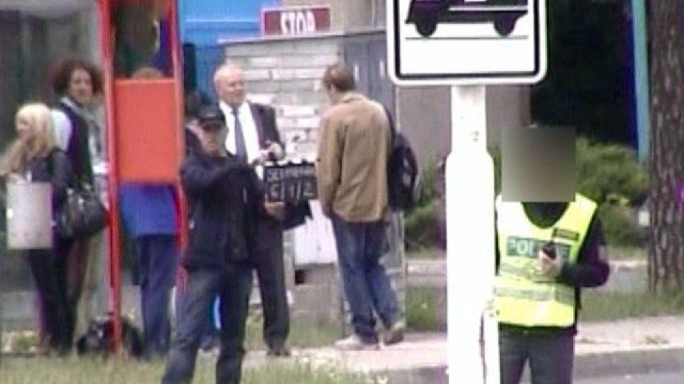 Na snímku je jeden z obviněných při nelegální práci pro filmovou produkci (v uniformě vedle dopravní značky).