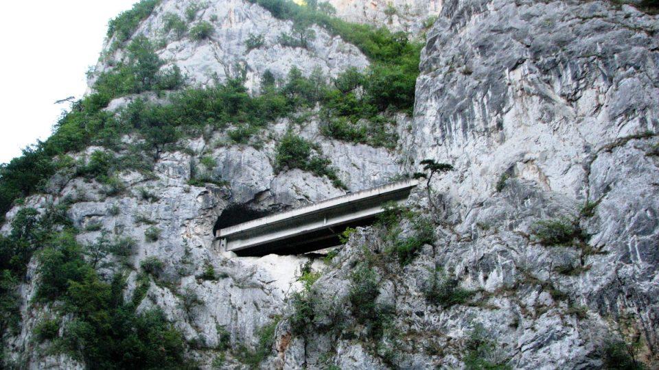 Vysoko nad námi protíná skály silnice, která mizí v nesčetných tunelech
