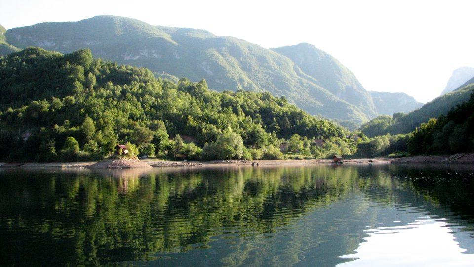 Poklidná hladina Višegradské přehrady a břehy bez jinak všudypřítomných turistů