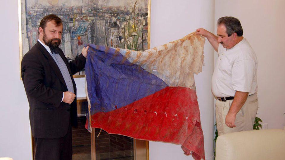 Česká vlajka vytažená z trosek na Ground Zero – drží ji někdejší velvyslanec ČR při OSN v New Yorku Hynek Kmoníček a jeden z newyorských hasičů