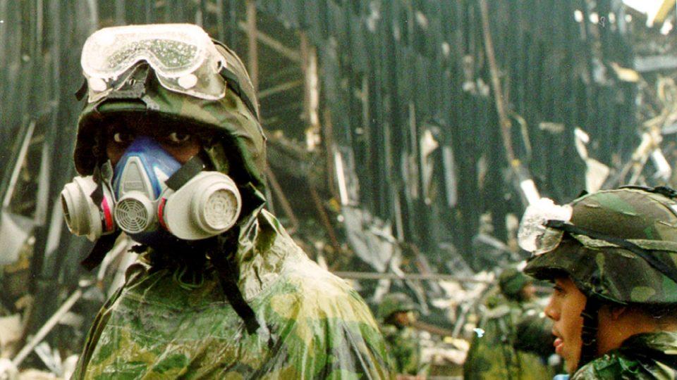 Vojáci národní gardy se chrání před oblaky prachu v okolí zničených mrakodrapů po teroristickém útoku v září 2001
