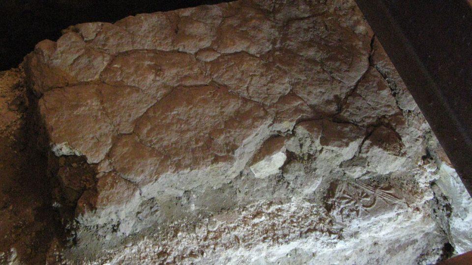 Udusaná hlína jako podlaha jedné fáze kostela a pod ní jedna dlaždice, jako ukázka další fáze podlahy