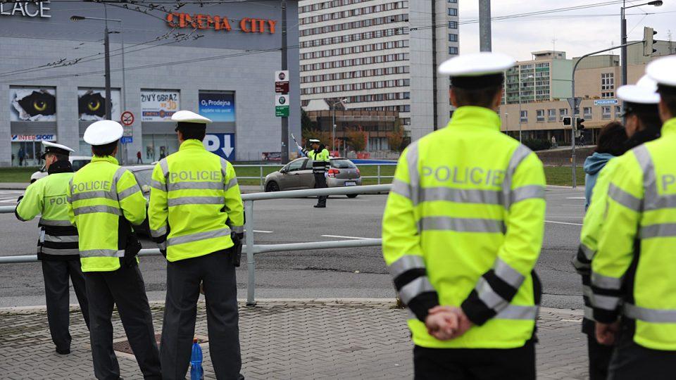 Policisté sledují svého kolegu při řízení křižovatky