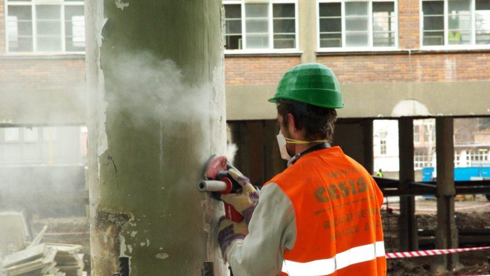 Dělník obrušuje konstrukci staré baťovy továrny