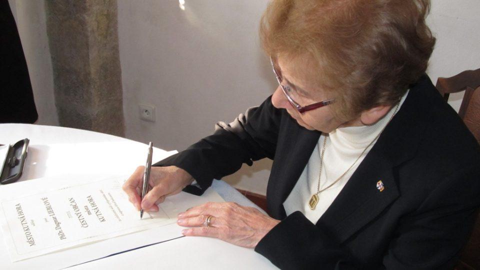 Dagmar Lieblová se podepisuje pod glejt Čestného občana Kutné Hory
