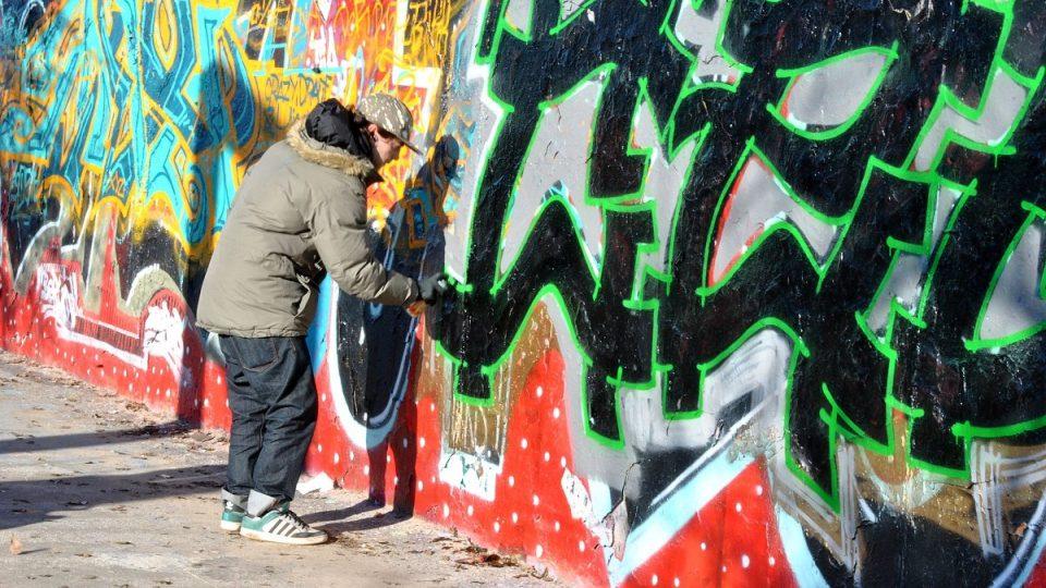 Mladí lidé sprejují po zdi, která kdysi dělila východní a Západní Berlín