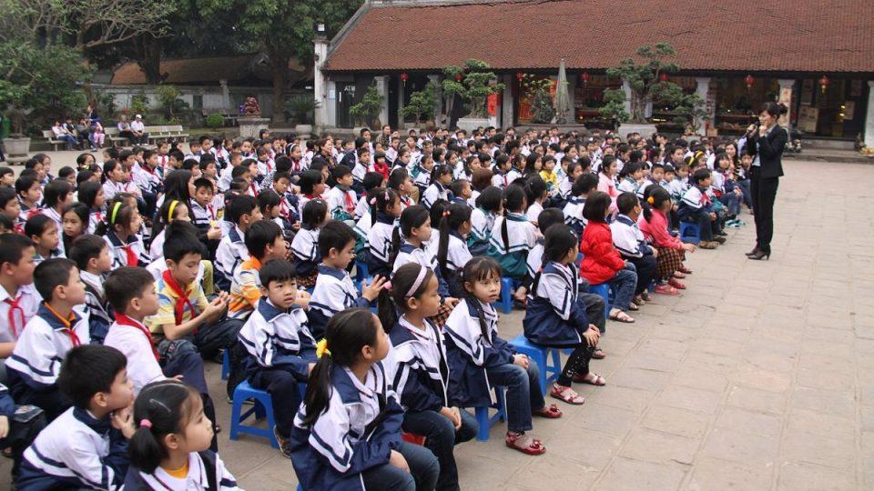 Desítky dětí posedávají na hlavním nádvoří a naslouchají vyprávění soudružky učitelky