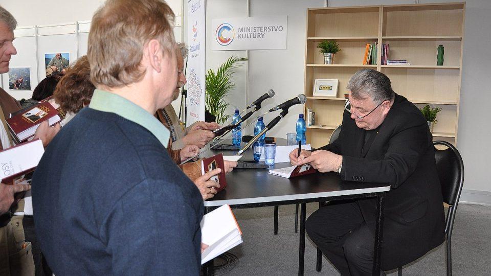 Kardinál podepisuje svou knihu Glosy Dominika Duky 2011