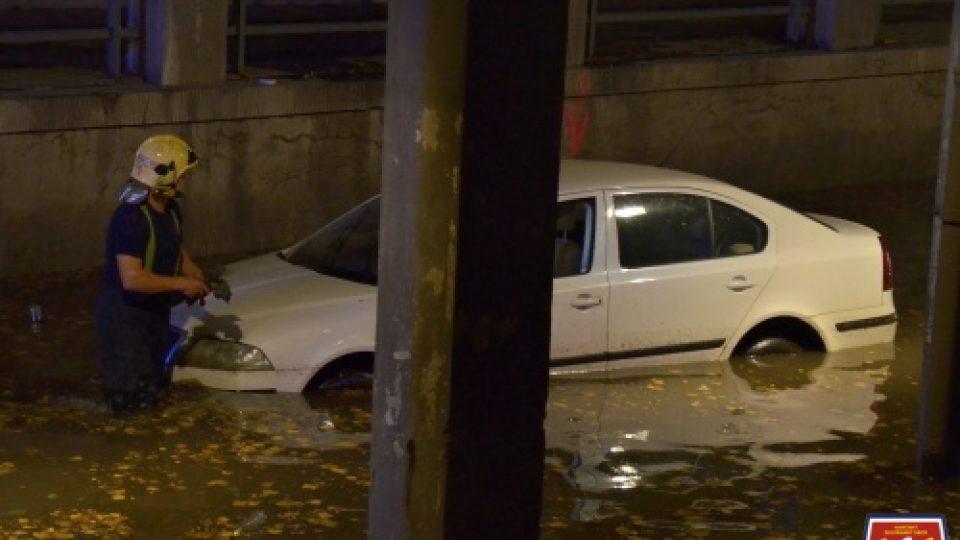 Hasiči vyprošťují auto ze zaplaveného podjezdu