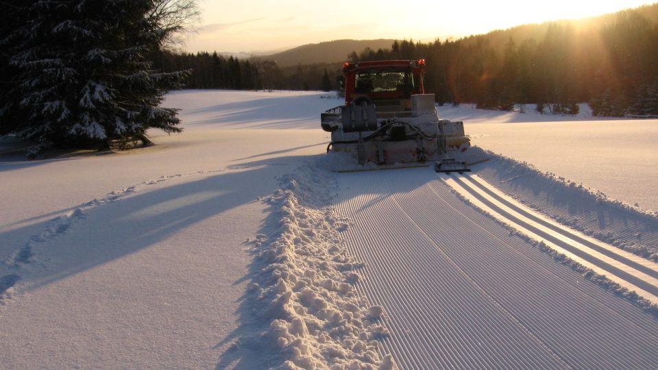 Sněhová rolba vykrajuje do čerstvého sněhu běžkařskou stopu
