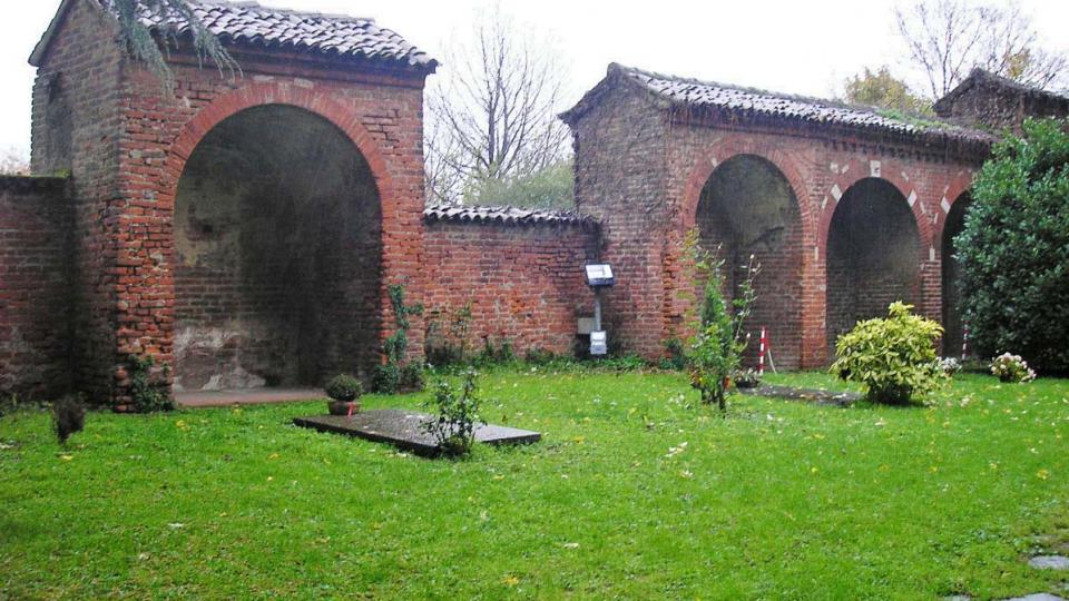Klášterní hřbitov v Chiaravalle za deštivého listopadového dne s náhrobní deskou Raffaela Mattioli