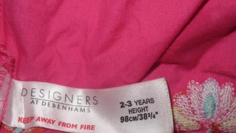 Holčička je oblečená do růžových šatů