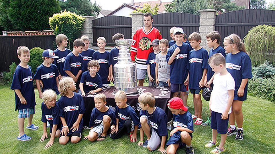 Michael Frolík pózuje s dětmi a Stanley Cupem
