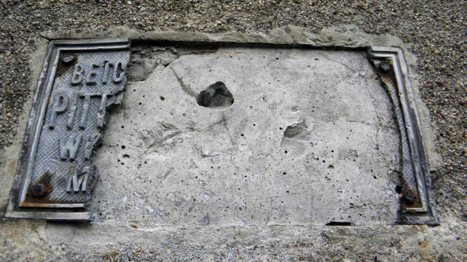 Zničená cedule na zdi kolem hrobky Kleinů v Loučné