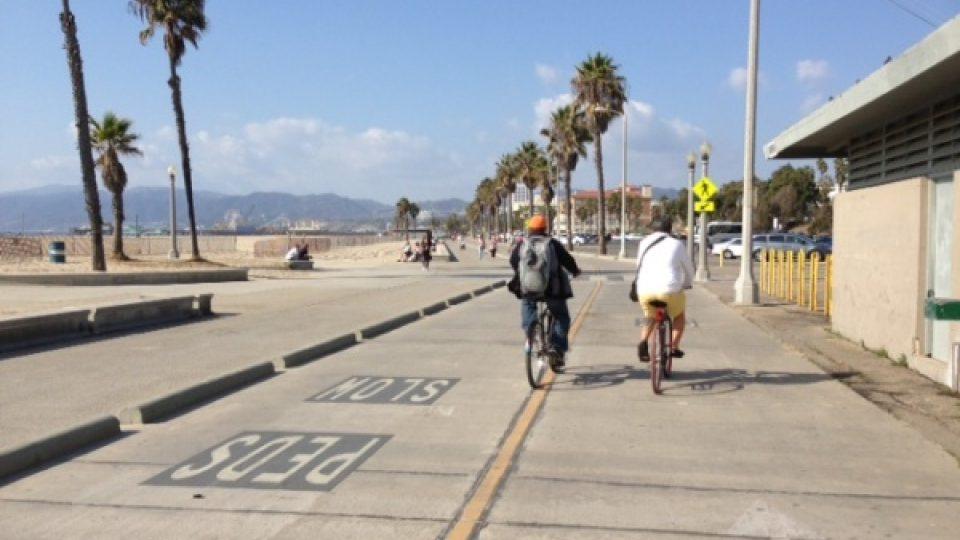Cyklisté na vypůjčených kolech se projíždějí kolem břehů oceánu