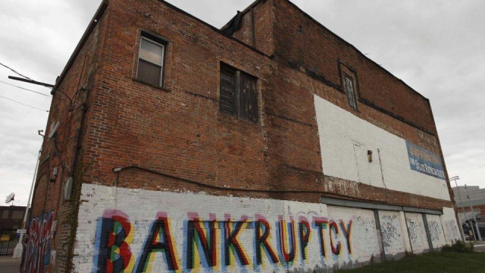Slovo bankrot namalované na budově v Detroitu