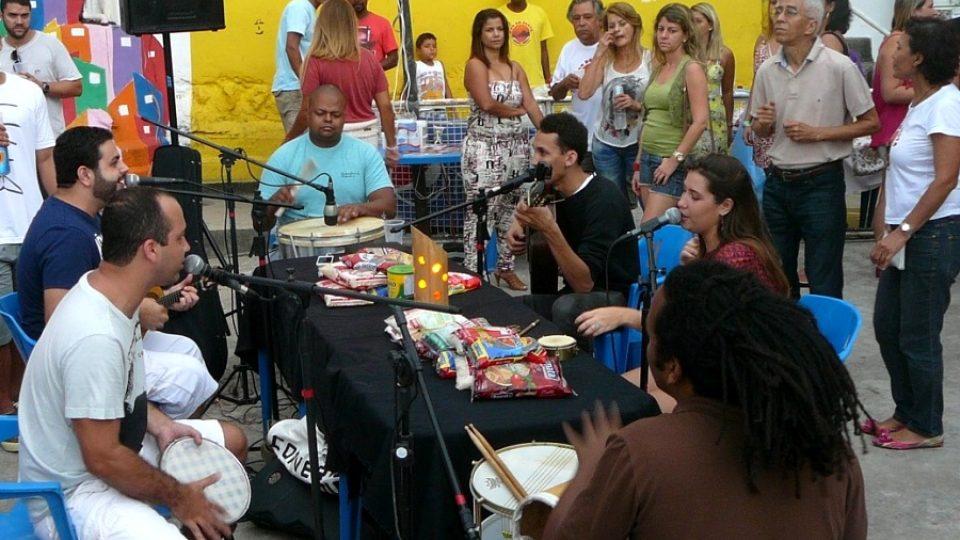 Lidé se pomalu scházejí a na stole mezi muzikanty se hromadí darované jídlo pro zdejší školku