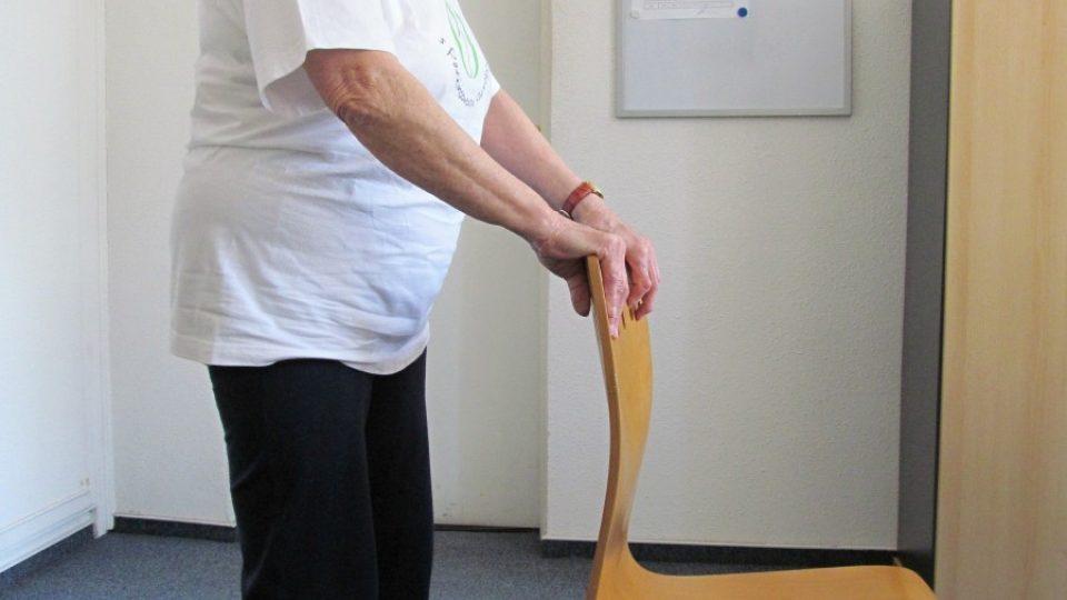 1. Základní postoj je stání se vzpřímenými zády, zvednutou bradou a rukama, které se přidržují opěradla židle.