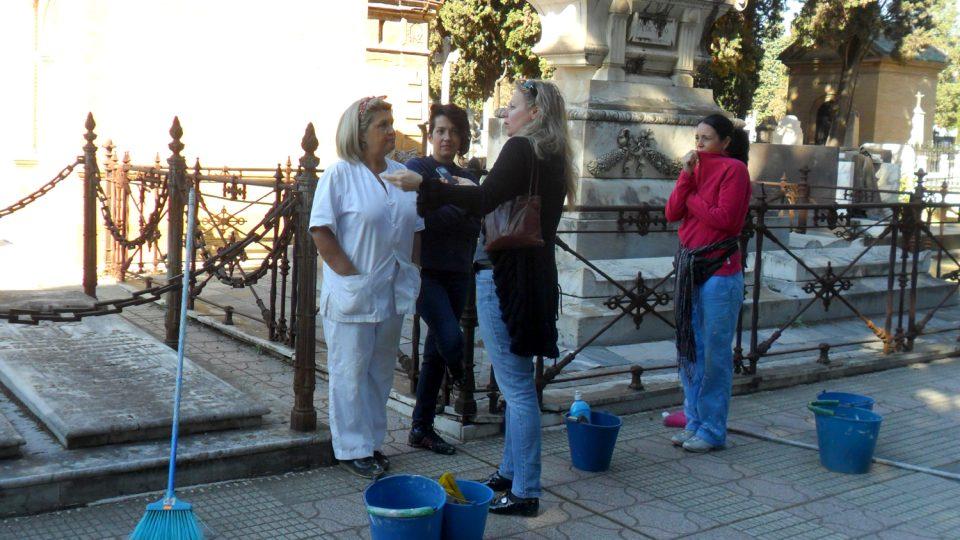 Tři energické ženy s kyblíky, košťaty a čistícími potřebami živě konverzovaly i při čištění hrobů