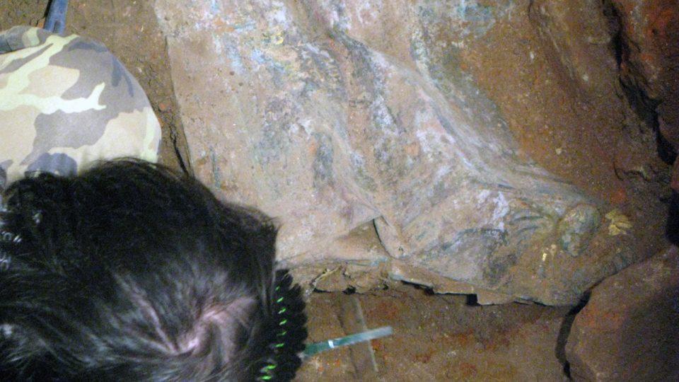 Postupně byla odkrývána čelní stěna rakve, kde se objevil úchyt a zlacená hlava anděla s křídly