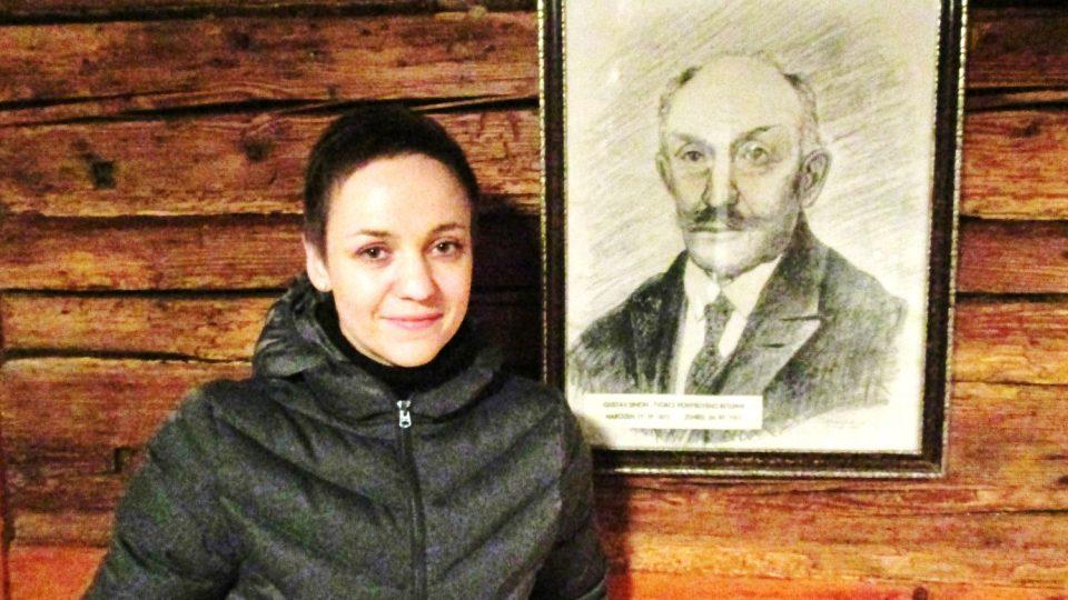 Portrét Gustava Simona, u něj stolí jeho pravnučka Lucie Kubátová, která dnes betlém ukazuje návštěvníkům