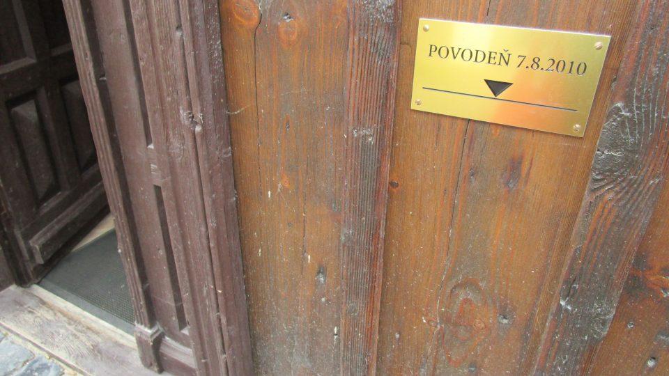 U vchodových dveří roubenky je štítek, který připomíná, pokud až sahala voda během srpnových povodních v roce 2010