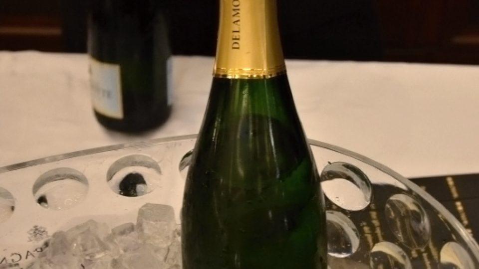 Číšník odstraňuje kapsli z lahve champagne Delamotte