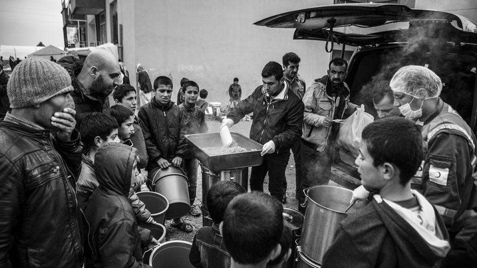 Dobrovolníci a zaměstnanci Červeného půlměsíce, mezinárodní neziskové organizace, která má stejná poslání a cíle jako mateřský Červený kříž, se starají o zásobování uprchilckého tábora