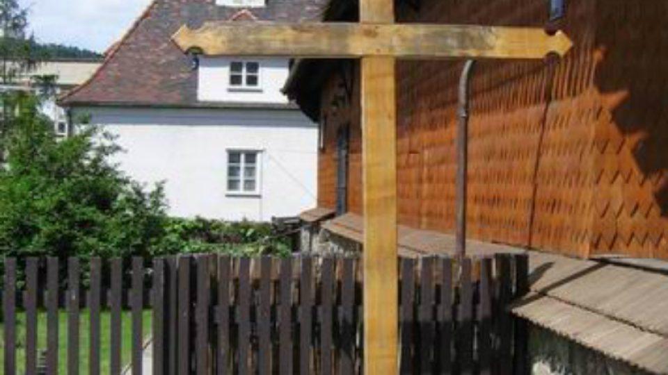 Vedle vchodu do kostela se tyčí dřevěný kříž