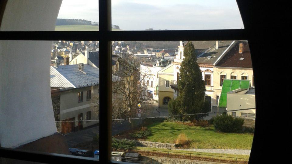 Výhled skrze okno v barokním štítu domu