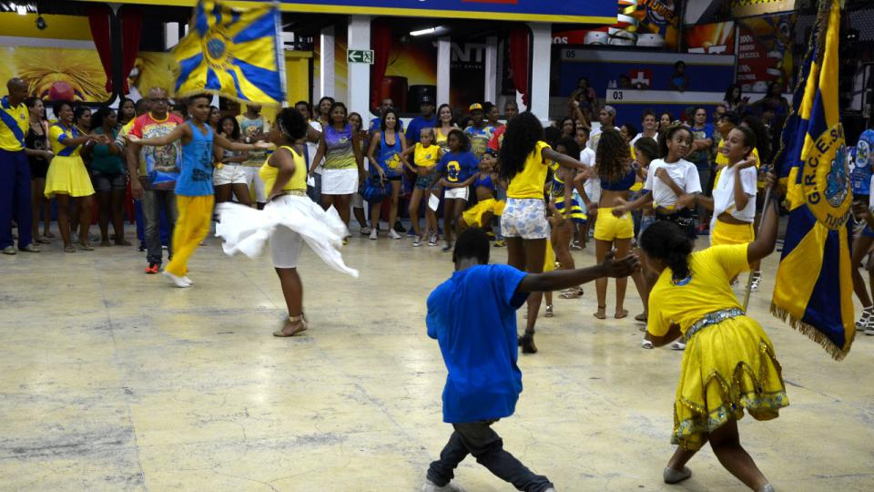 Děti se učí i mimo jiné uctívat vlajku, kterou vždy nese taneční pár. Vlajka je pro školy samby skoro posvátná věc