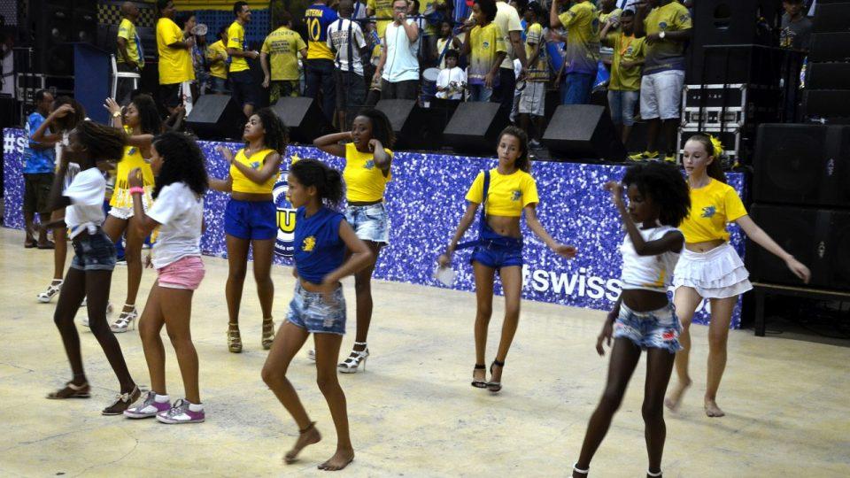 Na parketu mladé tanečnice tančí sambu do rytmu mladých bubeníků a melodie mladých zpěváků, kteří stojí na pódiu
