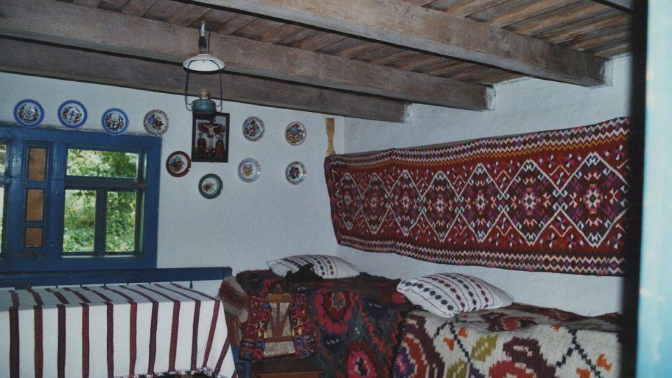 Interiér chalupy s malovanými závěsnými talířky a ručně tkaným kobercem na stěně