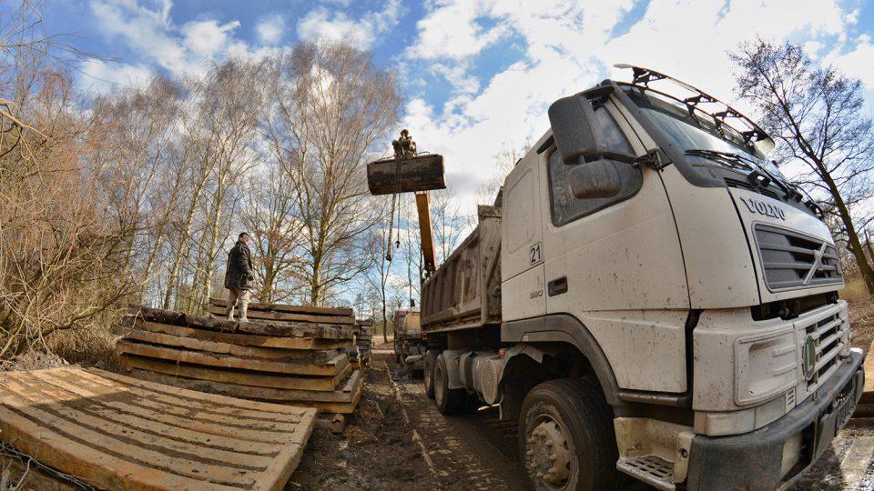 Ocelové panely slouží jako provizorní silnice a brání zapadnutí nákladních aut do bahna