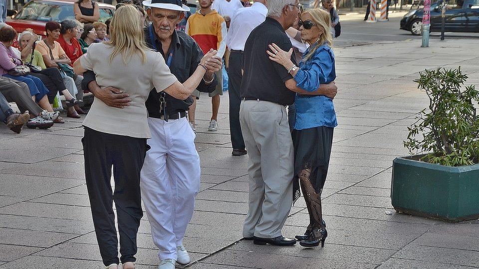 Organizátor tance na náměstí Daniel Prates - v bílém kloboučku - provádí jednu tanečnici za druhou