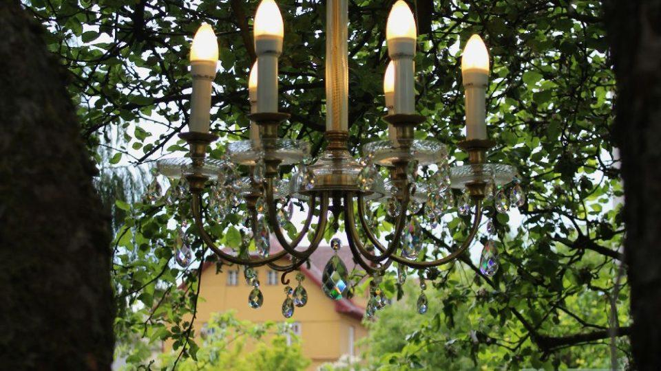 Součástí výstavy jsou i svítidla rozvěšená po stromech zahrady