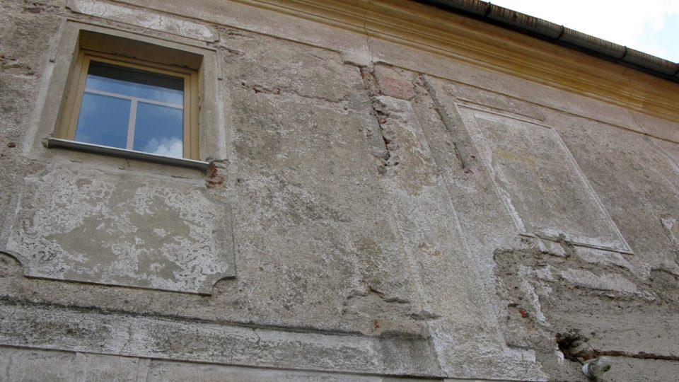 Ještě nerekonstruovaná zeď fary, kde je možné si všimnout zastavěného ostění okna