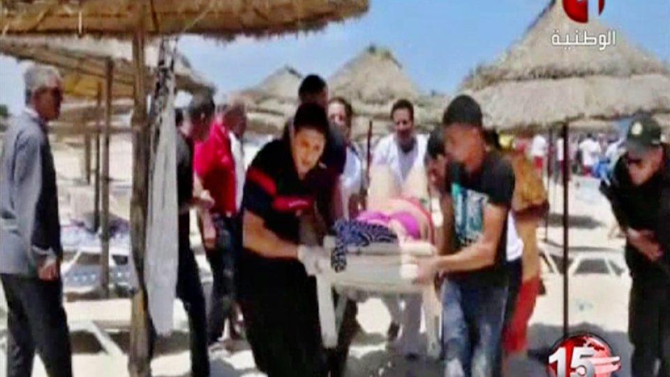 Zdravotníci na záběrech televize Tunisia TV1 odnášejí raněné z pláže po útoku atentátníka
