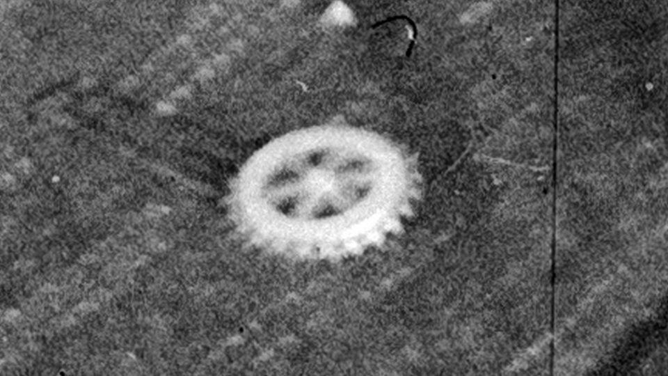 Odznak na klopě jeho saka lze díky velkému rozlišení negativu identifikovat jako odznáček Rotary Klubu