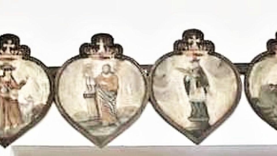 Pohřební štít srdcovitého tvaru ze železného plechu, mosazným páskem lemovaný, nahoře trojlistovité zakončení. Olejová malba sv. (Martin, Josef, Jan Nepomucký, Lukáš, Notburga, Roch) nad ním korunka s křížem. Lidová práce