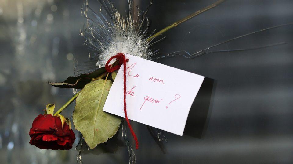 """Růži s lístkem, na němž stojí """" Ve jménu čeho?"""" někdo umístil do rozstříleného okna restaurace na Rue de Charonne v Paříži"""