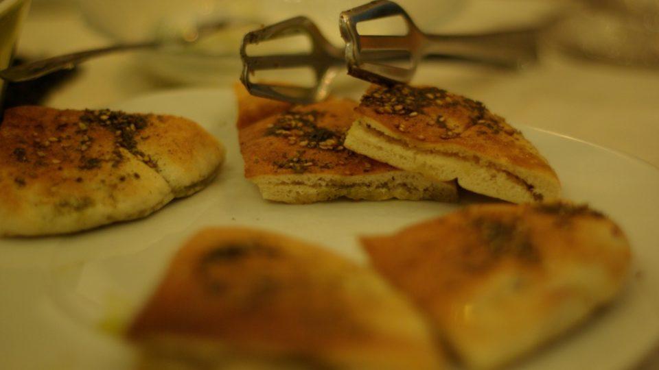 Přikusuje se arabský chléb zapečený s olivovým olejem a směsí koření zátar